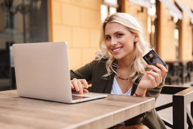 Portret adorable blond kobieta ubrana w kurtkę za pomocą srebrnego laptopa i trzymając kartę kredytową, siedząc w kawiarni na świeżym powietrzu