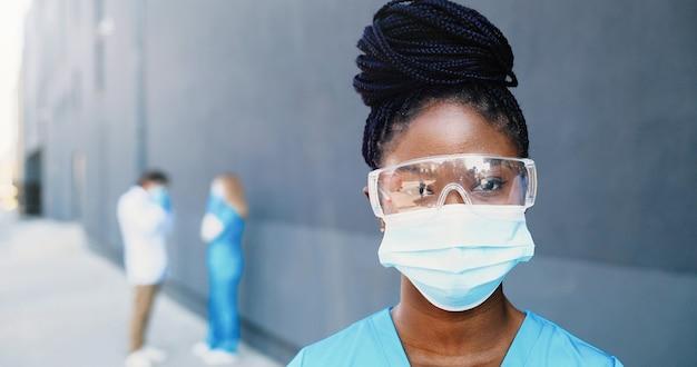 Portret african american piękna kobieta lekarz w masce medycznej i gogle patrząc na kamery. zamknij się kobieta lekarz w ochronie dróg oddechowych. lekarze w tle. zbliżenie. dolly strzał