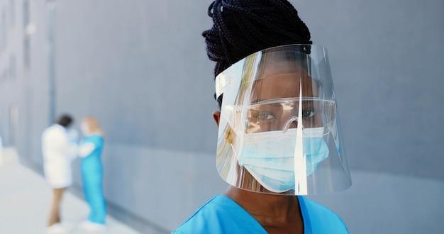 Portret african american piękna kobieta lekarz w maskę medyczną, osłonę twarzy i okulary patrząc na kamery. zamknij się kobieta lekarz w ochronie dróg oddechowych. lekarze w tle. kombinezon chroniony.