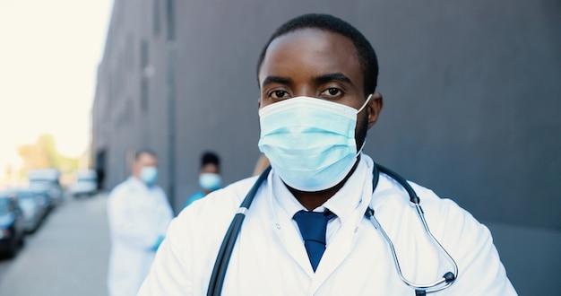 Portret african american przystojny mężczyzna lekarz w masce medycznej i patrząc na kamery ze stetoskopem. zbliżenie na medyka w ochronie dróg oddechowych. lekarze ras mieszanych na tle.