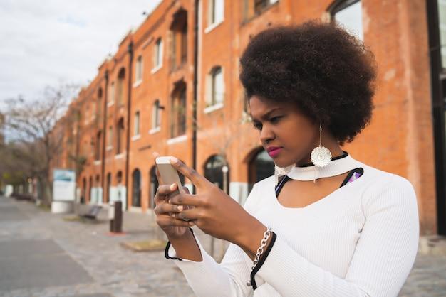 Portret afro american łacińskiej kobiety za pomocą swojego telefonu komórkowego na zewnątrz na ulicy. koncepcja miejska i komunikacyjna.