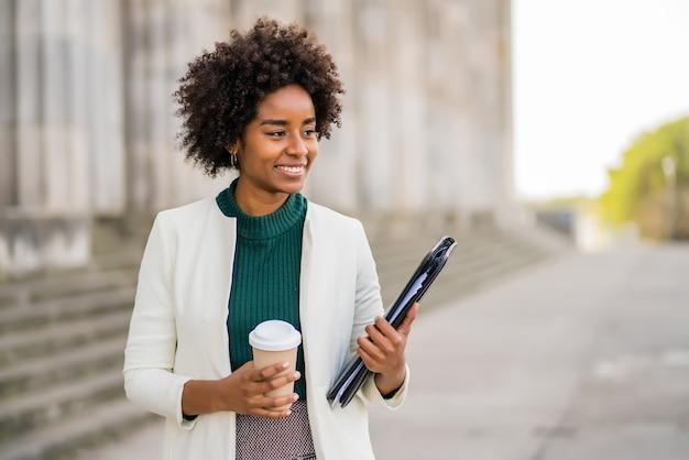 Portret Afro Bizneswoman Trzyma Filiżankę Kawy I Schowek Podczas Spaceru Na Ulicy Na Ulicy. Koncepcja Biznesowa I Miejska. Premium Zdjęcia