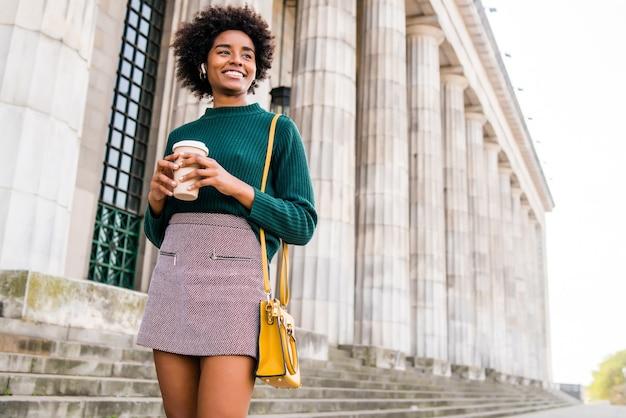 Portret afro bizneswoman trzyma filiżankę kawy podczas spaceru na ulicy na ulicy. koncepcja biznesowa i miejska.