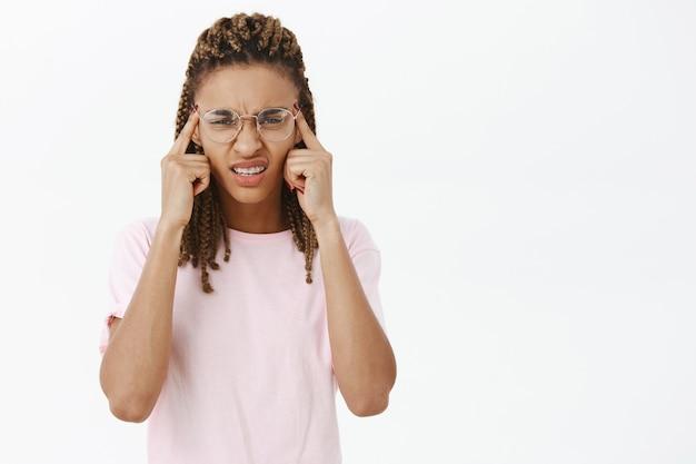 Portret afro-dziewczyna w okularach mrużąc oczy, mając problemy ze wzrokiem