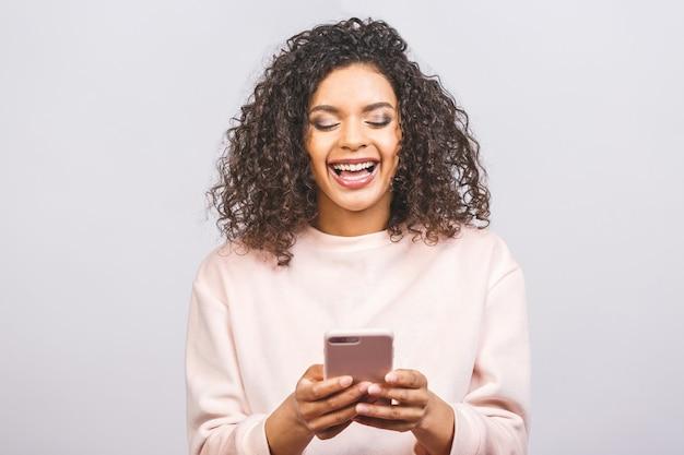 Portret afroamerykanin ładny atrakcyjny piękny wesoły optymistyczny falistowłosa dziewczyna za pomocą nowego urządzenia gadżet na białym tle nad białym tle.