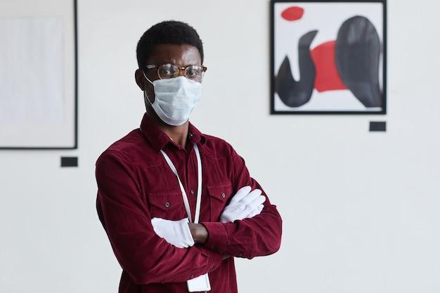 Portret afroamerykanina w masce w pasie, stojącego z rękami skrzyżowanymi na tle nowoczesnych grafik w galerii sztuki,