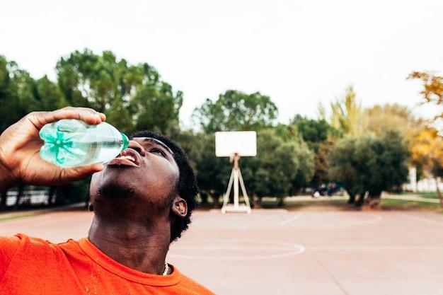 Portret afroamerykanów czarny chłopiec wody pitnej po treningu na boisku miejskim do koszykówki. ubrana w pomarańczowy t-shirt.