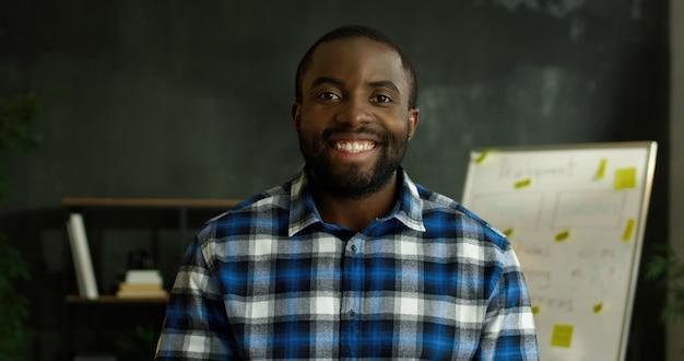 Portret afroamerykanów wesoły przystojny mężczyzna w motley koszuli stojący w pokoju biurowym i uśmiechając się radośnie do kamery.