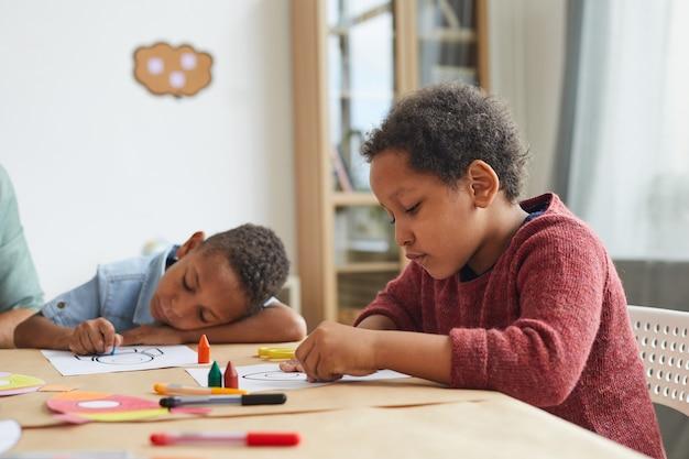 Portret afroamerykańskiego chłopca rysującego obrazki kredkami podczas zajęć plastycznych w przedszkolu