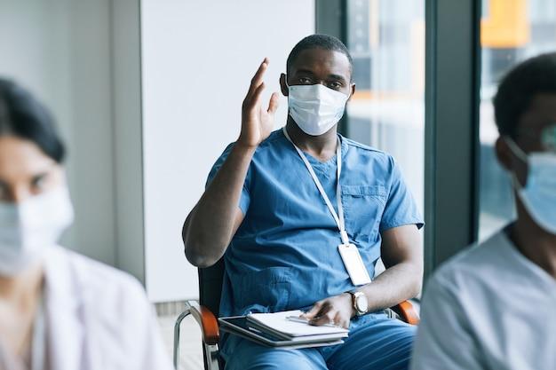 Portret afroamerykańskiego medyka podnoszącego rękę, aby zadać pytanie podczas seminarium lub konferencji, skopiuj miejsce