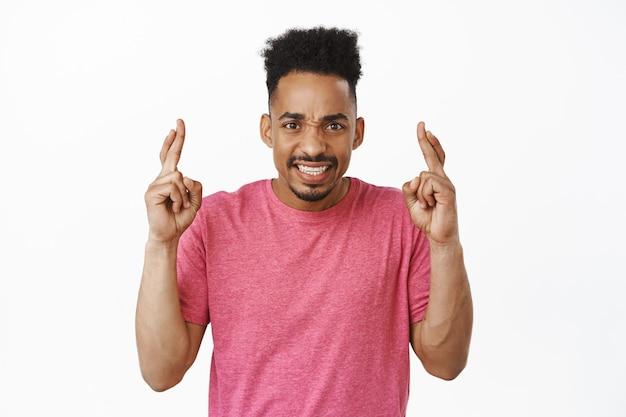 Portret afroamerykańskiego mężczyzny krzyżują palce na szczęście, życząc, uśmiechając się optymistycznie, czekając na dobre wieści, módlcie się o spełnienie marzeń na białym