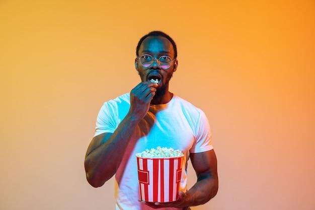 Portret afroamerykańskiego mężczyzny na białym tle na gradientowej pomarańczy w świetle neonowym