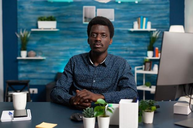 Portret afroamerykańskiego mężczyzny patrzącego w kamerę przy biurku, młody czarny mężczyzna siedzący w przytulnym, nowoczesnym ...