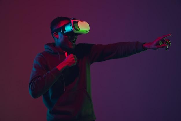 Portret afroamerykańskiego mężczyzny w zestawie słuchawkowym vr na białym tle na gradientowym tle studio w świetle neonowym. piękny męski model. pojęcie ludzkich emocji, wyrazu twarzy, sprzedaży, reklamy, włączenia, technologii.