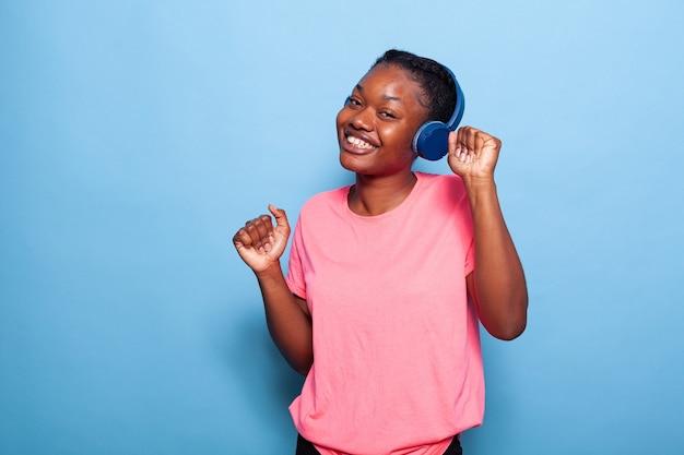 Portret afroamerykańskiego nastolatka tańczącego samotnie w studio na niebieskim tle