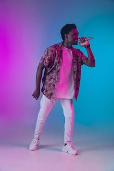 Portret afroamerykańskiego piosenkarza męskiego na tle gradientowego studia w świetle neonowym