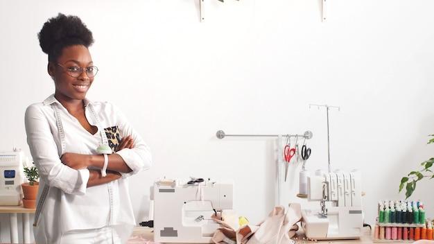 Portret afroamerykańskiego projektanta mody pracującego w studiu, uśmiechnięty projektant mody patrzy w kamerę