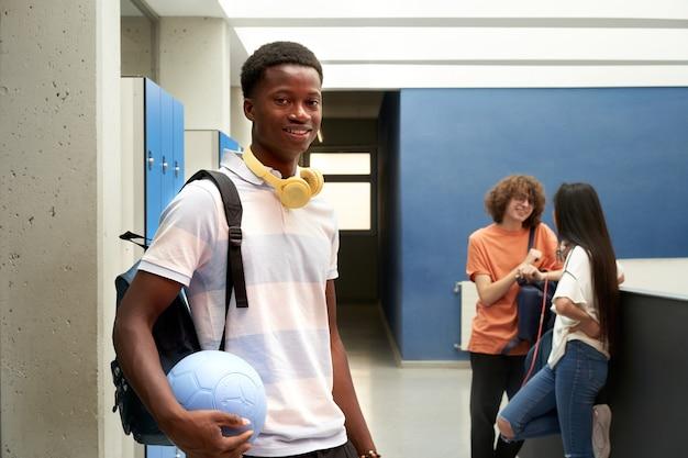 Portret afroamerykańskiego studenta patrzącego w kamerę na szkolnym korytarzu i trzymającego piłkę