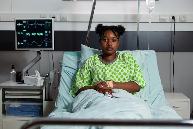 Portret afroamerykańskiej dziewczyny siedzącej na oddziale szpitalnym