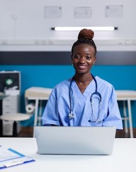 Portret afroamerykańskiej pielęgniarki korzystającej z laptopa przy białym biurku