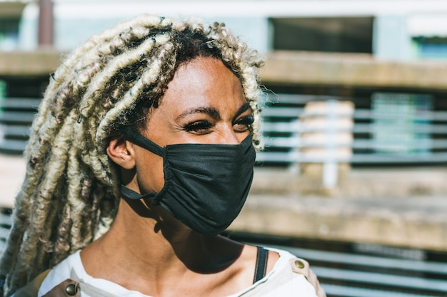 Portret afrykańska dziewczyna jest ubranym twarzy ochronną maskę z blond dreadlocks