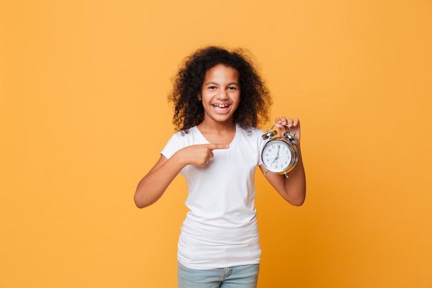 Portret afrykańska dziewczyna wskazuje palec przy budzikiem