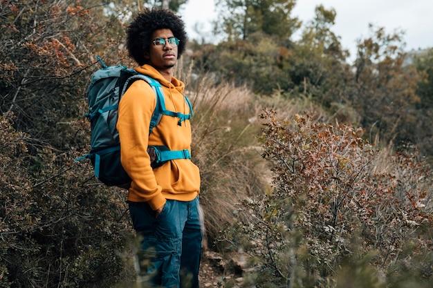 Portret afrykański męski wycieczkowicz wycieczkuje w lesie