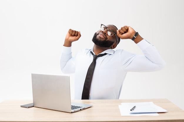 Portret afrykański mężczyzna dosypianie przy jego miejscem pracy na popielatym tle
