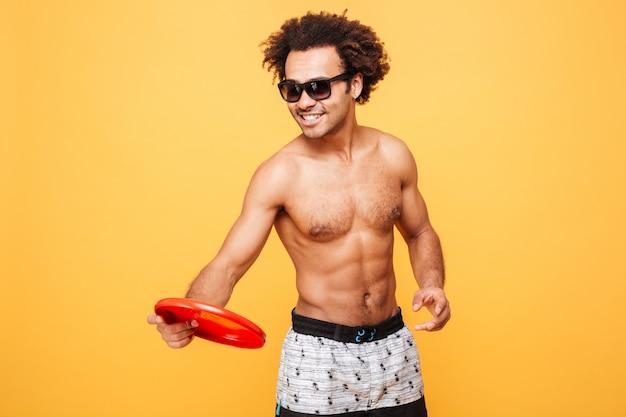 Portret afrykański mężczyzna trzyma frisbee w okularach przeciwsłonecznych