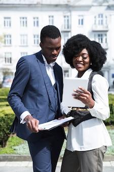 Portret afrykański młody biznesmen i bizneswoman patrzeje cyfrową pastylkę