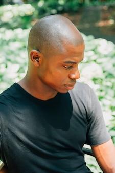 Portret afrykański młody człowiek patrzeje daleko od przy outdoors