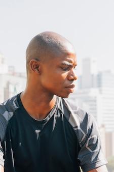 Portret afrykański ogolony młody człowiek patrzeje nad ramieniem