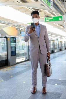 Portret afrykańskiego biznesmena na peronie dworca kolejowego w masce na twarz