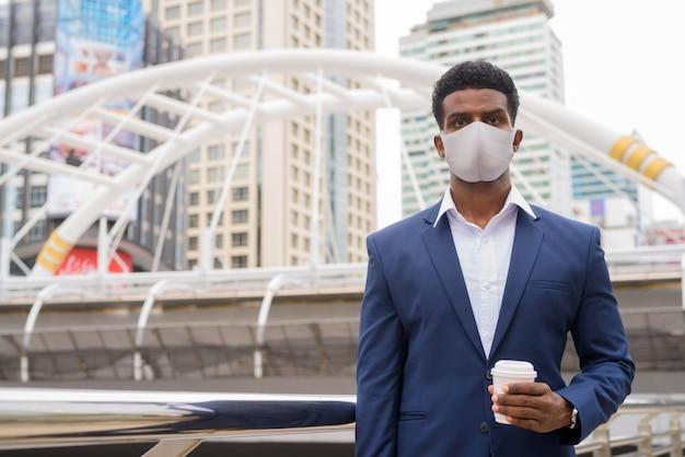 Portret afrykańskiego biznesmena noszącego maskę na zewnątrz i trzymającego filiżankę kawy na wynos, ujęcie poziome