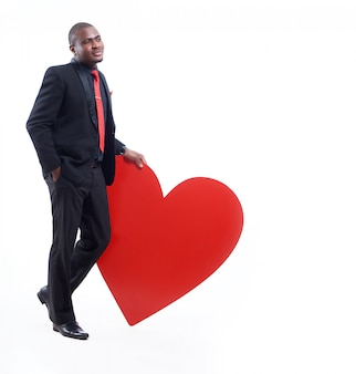 Portret afrykańskiego biznesmena w czarnym apartamencie i czerwonym krawacie, pozowanie i opierając się wielkim czerwonym sercem.