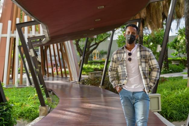 Portret afrykańskiego czarnego mężczyzny na zewnątrz w mieście latem, noszącego maskę na twarz, ujęcie poziome