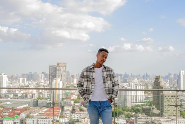 Portret afrykańskiego czarnego mężczyzny na zewnątrz w mieście na dachu podczas letniego ujęcia poziomego