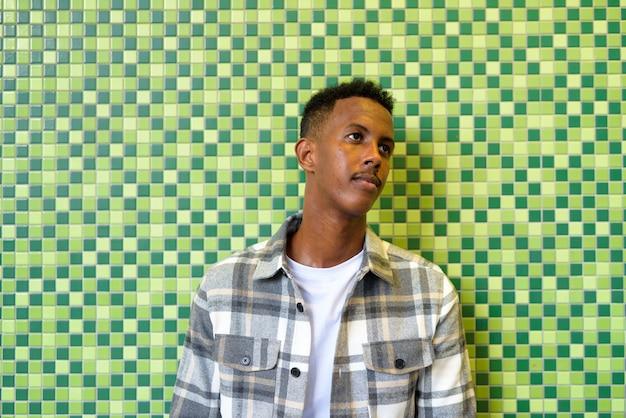 Portret afrykańskiego czarnego mężczyzny na zewnątrz w mieście, opierając się o ścianę w nocy podczas myślenia