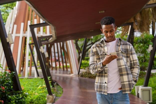 Portret afrykańskiego czarnego mężczyzny na zewnątrz w mieście podczas letniego ujęcia poziomego