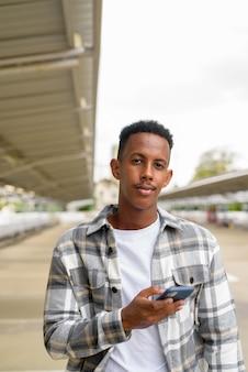 Portret afrykańskiego czarnego mężczyzny na zewnątrz w mieście przy użyciu telefonu komórkowego latem