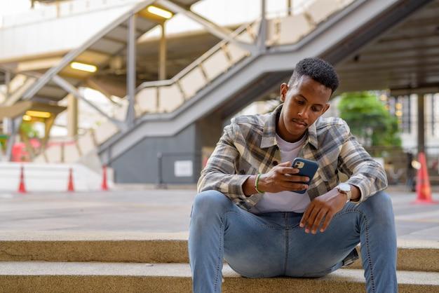 Portret afrykańskiego czarnego mężczyzny siedzącego na zewnątrz w mieście latem przy użyciu poziomego ujęcia telefonu komórkowego mobile