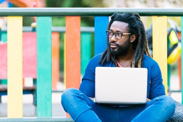 Portret afrykańskiego człowieka siedzącego na zewnątrz z laptopem. koncepcja pracy miejskiej