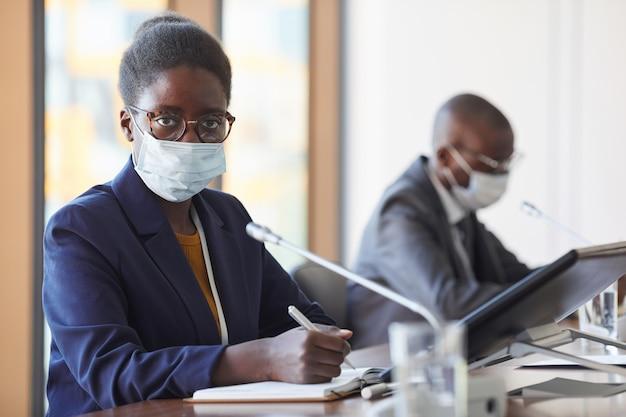 Portret afrykańskiego interesu w masce ochronnej patrząc podczas pracy na konferencji podczas pandemii