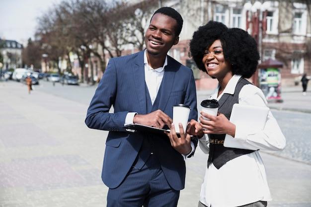 Portret afrykańskiego młodego biznesmena i bizneswoman trzyma jednorazową filiżankę w mieście