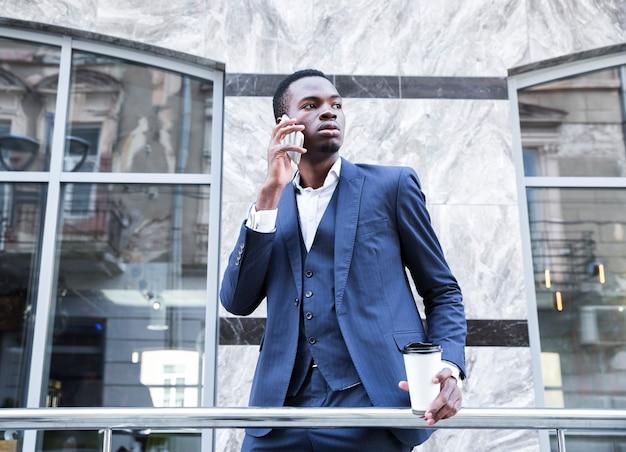 Portret afrykańskiego młodego biznesmena mienia jednorazowa filiżanka kawy opowiada na telefonie komórkowym