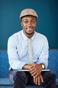 Portret afrykańskiego młodego biznesmena siedzi z laptopem i uśmiecha się w biurze