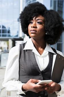 Portret afrykańskiego młodego bizneswomanu mienia telefon komórkowy w ręce patrzeje daleko od
