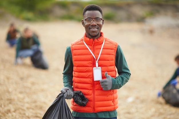 Portret afrykańskiego młodego człowieka, trzymając worek ze śmieciami i uśmiechając się do kamery, stojąc na zewnątrz