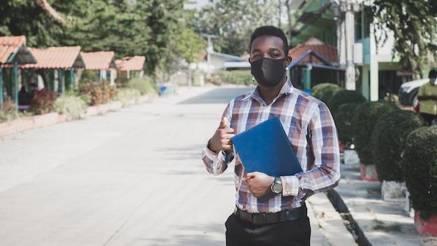 Portret afrykańskiego nauczyciela w masce stojącej na zewnątrz w szkole