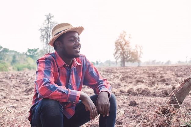 Portret afrykańskiego rolnika mężczyzna obsiadanie przy polem